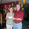 Arlin presenting $200 check to Kathy, daughter of Arnold Dugmore, from the Arnold Dugmore Memorial Shoot.